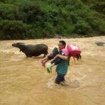 中国で最も危険な通学路と言われている場所を渡る先生と児童たち。雨の降った日は渡るのに一苦労。
